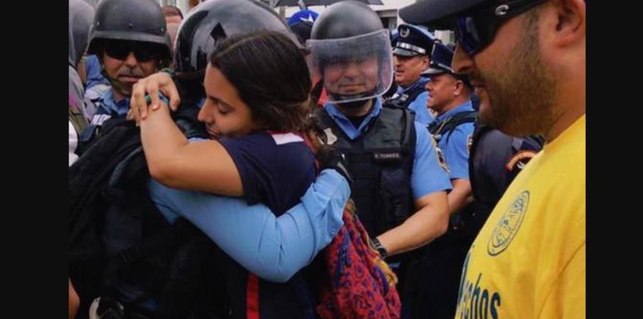 Capturan el momento de un abrazo entre un policía y una manifestante (horizontal-x3)