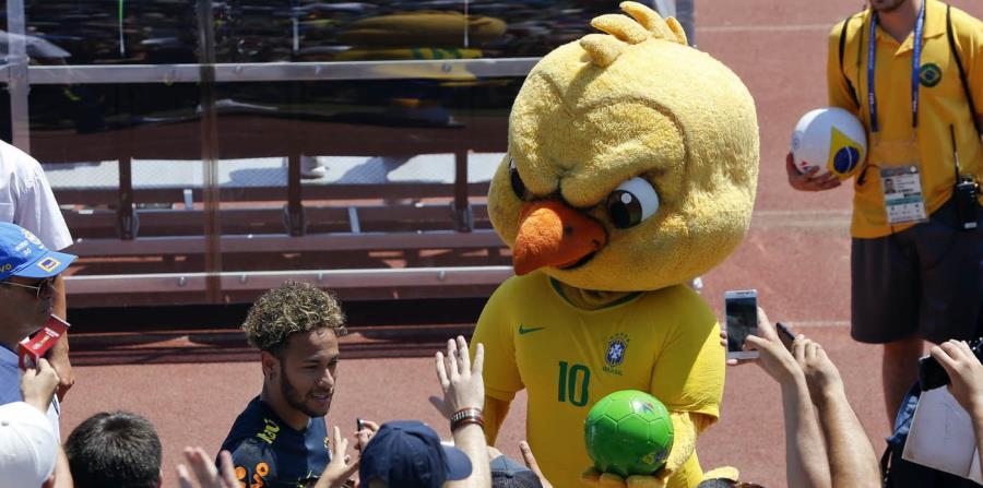 En esta foto del 12 de junio de 2018, Canarinho, la mascota de Brasil, sostiene un balón junto a Neymar, al final de un entrenamiento en Sochi, Rusia (horizontal-x3)