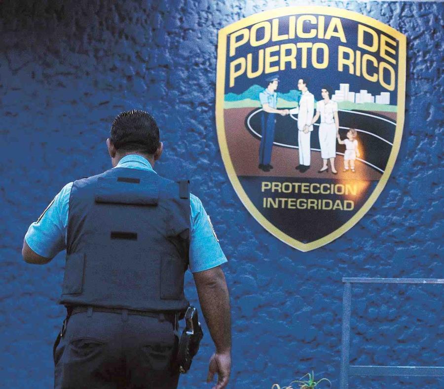 Un agente de la Policía pasa al lado del logo de este cuerpo de seguridad en Puerto Rico. (GFR Media) (semisquare-x3)