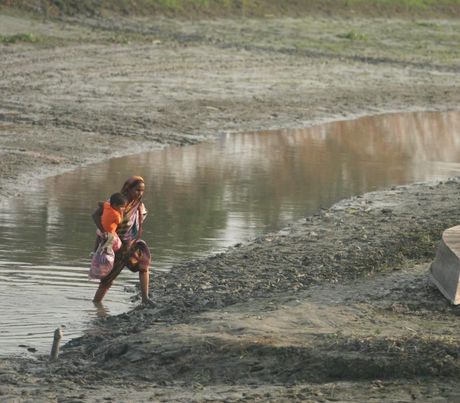 Una mujer camina por un canal casi seco con su hijo en brazos en la ciudad de Savar, Bangladesh (semisquare-x3)