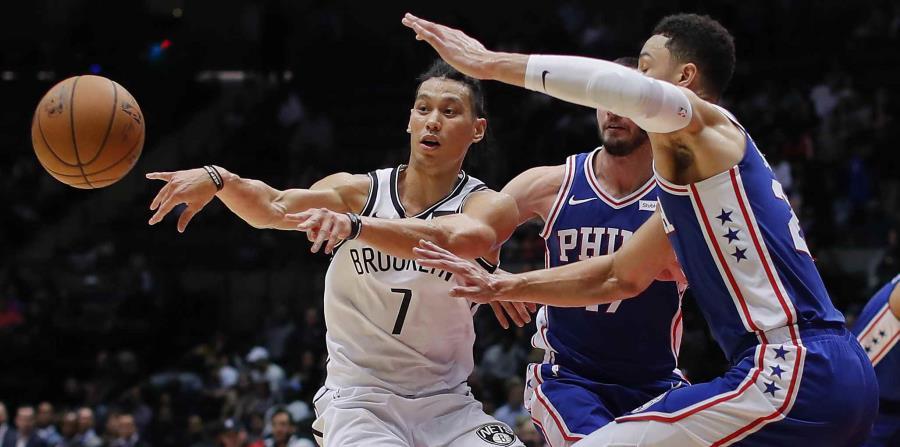 Jeremy Lin (7), de los Nets de Brooklyn, pasa el balón ante la marca de Ben Simmons, derecha, y JJ Redick (17), de los 76ers de Filadelfia, en un juego de pretemporada en Uniondale, Nueva York. (AP (horizontal-x3)