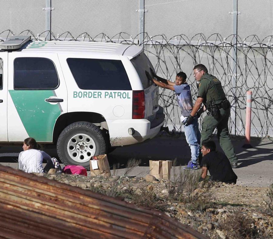 En esta fotografía de 2018, unos solicitantes de asilo hondureños son detenidos por los agentes de la Patrulla Fronteriza de Estados Unidos tras cruzar el muro fronterizo. (AP) (semisquare-x3)