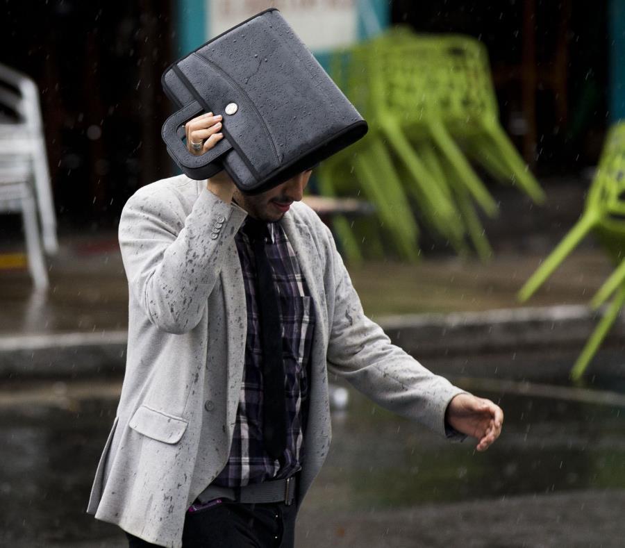 Un hombre se escuda con un portafolio de la lluvia. (GFR Media) (semisquare-x3)