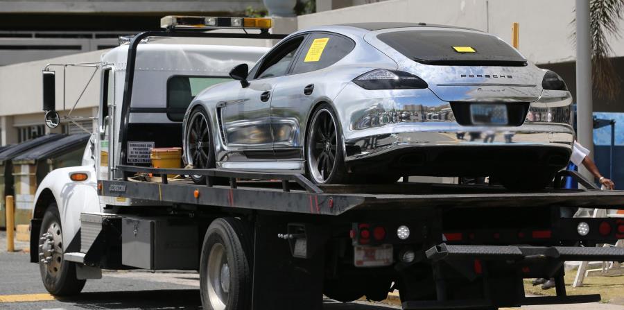 Momento en que una grúa llega al Departamento de Hacienda con el Porsche Panamera, del año 2011, embargado. (horizontal-x3)