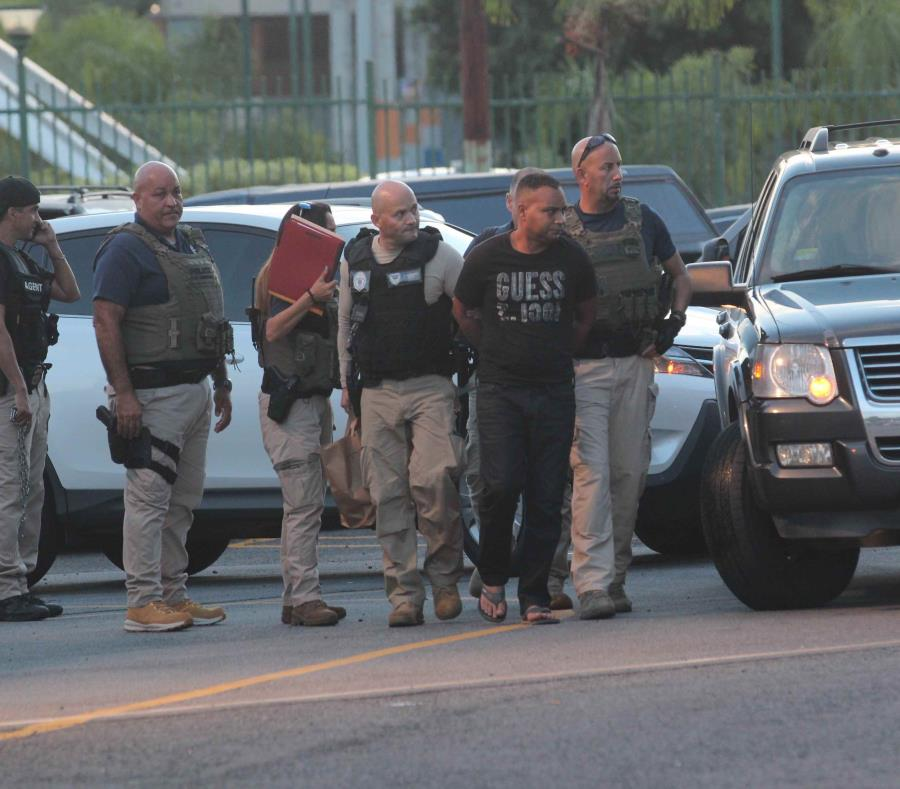 Dos agentes del  Servicio de Inmigración y Control de Aduanas (ICE-HSI, por sus siglas en inglés) trasladan a un hombre arrestado. (GFR Media) (semisquare-x3)