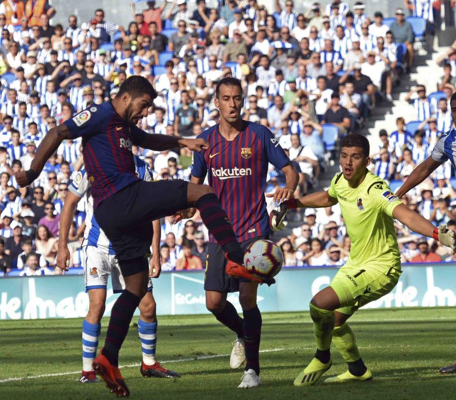 El delantero uruguayo Luis Suárez (izquierda) anota el primer gol del Barcelona en el partido contra la Real Sociedad, el sábado 15 de septiembre de 2018 en San Sebastián, España (semisquare-x3)