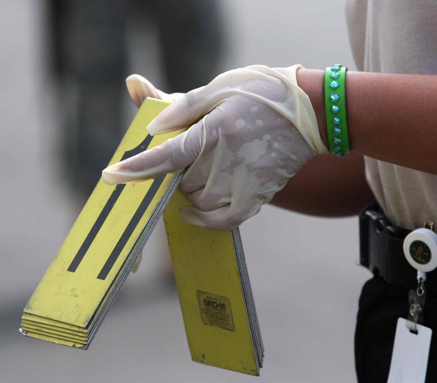 Un agente de la Policía coloca los números que identifican la prueba encontrada en una escena. (GFR Media) (semisquare-x3)