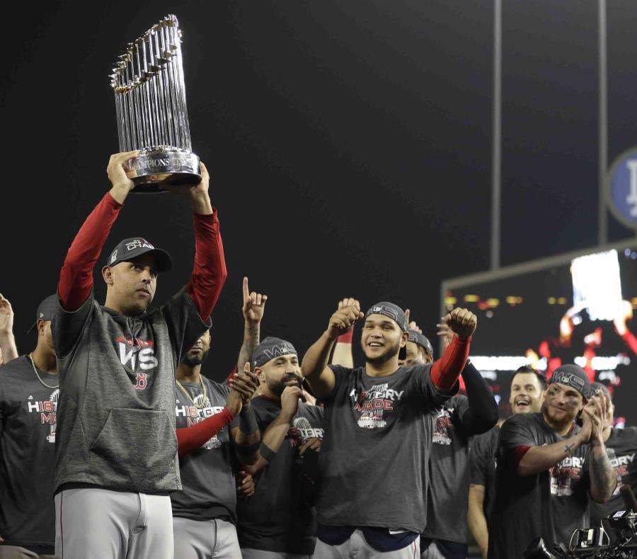 El dirigente cagueño Alex Cora alza el trofeo de campeonato de la Serie Mundial luego que los Medias Rojas eliminaron a los Dodgers de Los Ángeles.  (AP / Jae C. Hong) (semisquare-x3)