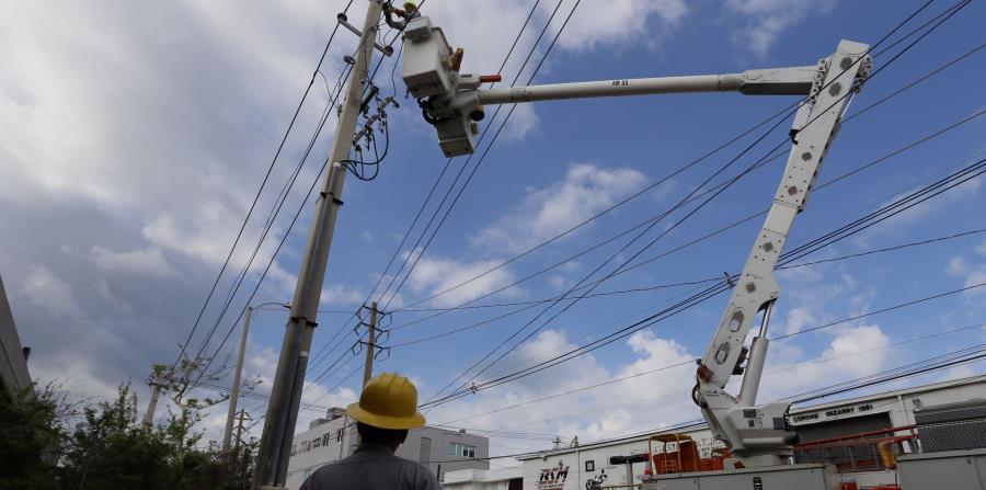 Dos empleados de la AEE reparan la electricidad en Santurce. (EFE) (horizontal-x3)