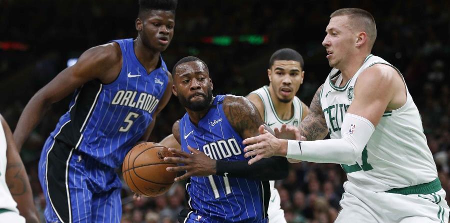 Jonathon Simmons, del Magic de Orlando, conduce el balón junto a Daniel Theis, de los Celtics de Boston, en el encuentro disputado hoy. (AP) (horizontal-x3)