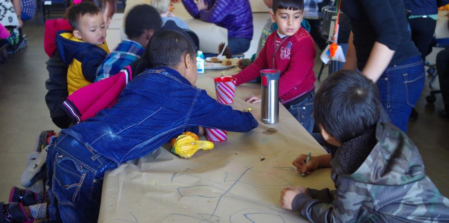 Unos niños inmigrantes de distintas razas juegan durante un almuerzo colectivo celebrado en la Escuela Comunitaria