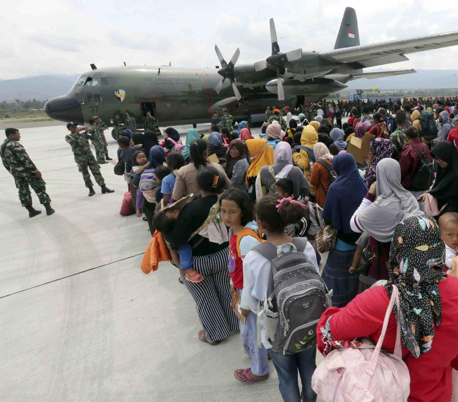 Un grupo de personas espera para embarcar en un avión de carga de la Fuerza Aérea en el aeropuerto Mutiara Sis Al-Jufri para salir de la ciudad de Palu, afectada por un sismo y un posterior tsunami, en el centro de la isla de Célebes, en Indonesia. (AP) (semisquare-x3)