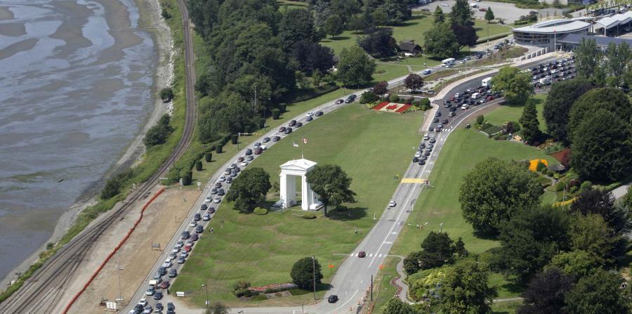 En esta fotografía de archivo del 24 de julio de 2009, varios vehículos hacen fila para cruzar hacia Estados Unidos, a la izquierda, y a Canadá, a la derecha, en la localidad canadiense de Boundary Bay, frente a Blaine, Washington. (AP) (horizontal-x3)