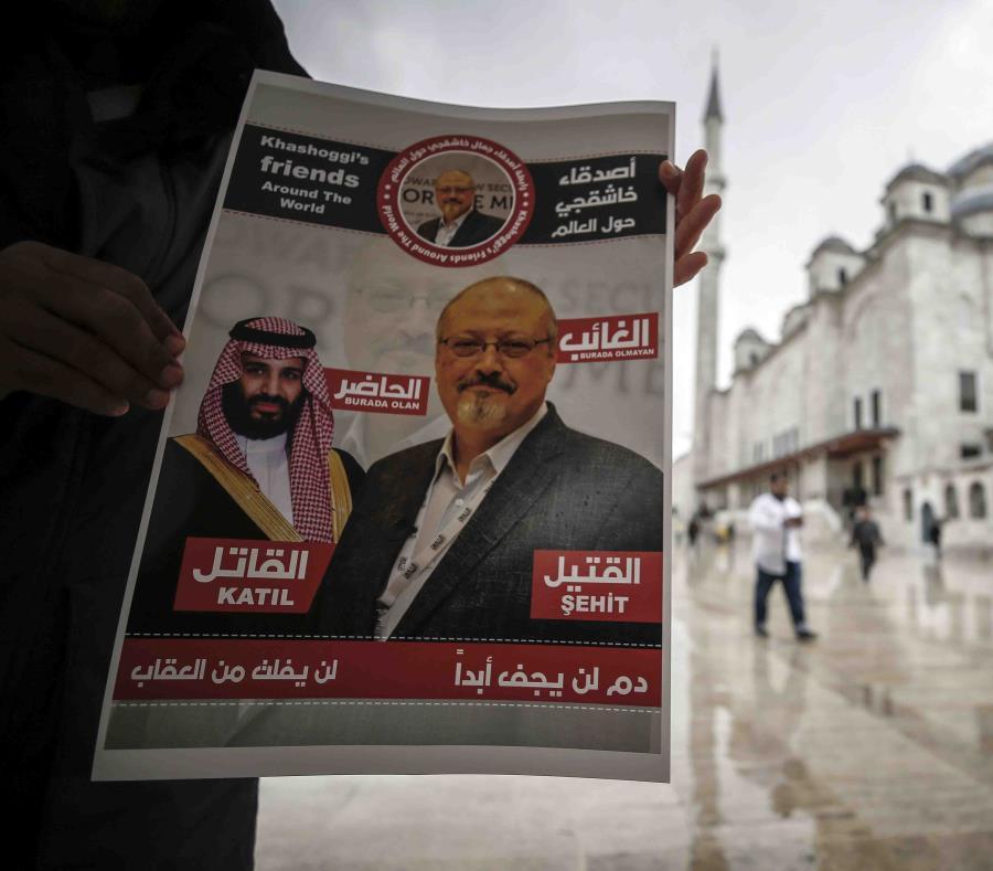 Un hombre sostiene un cartel que muestra imágenes del príncipe heredero saudí Muhammed bin Salman y del periodista Jamal Khashoggi, en el que se describe al príncipe como