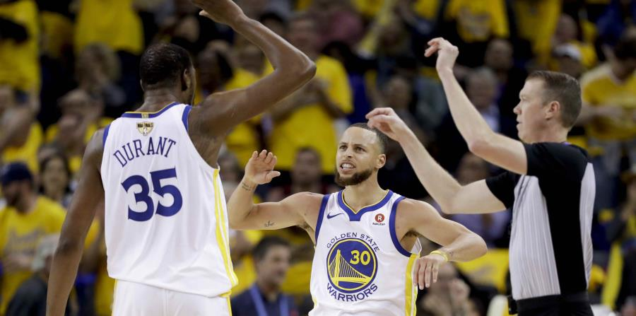 Kevin Durant y Stephen Curry, de los Warriors de Golden State, celebran una canasta. (AP) (horizontal-x3)
