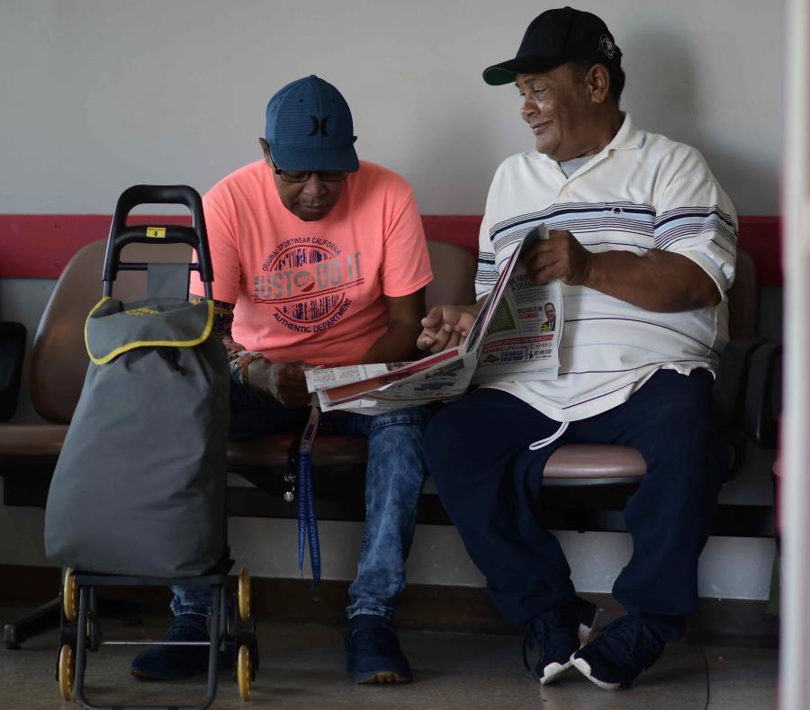 Los pacientes de diálisis Elías Salgado, de 56 años, y Edwin Alvarado, de 59, bromean mientras leen el periódico en el aeropuerto de Vieques, donde esperaban para embarcar en un avión que los trasladaría para recibir tratamiento. (semisquare-x3)