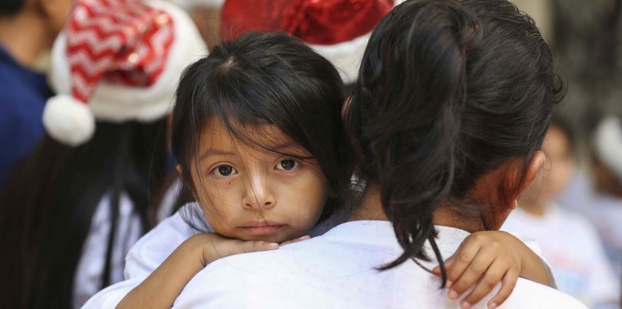 Lucia Quiej sostiene a su hija de cuatro años, Diana Jimenez, 4, en el marco de la campaña