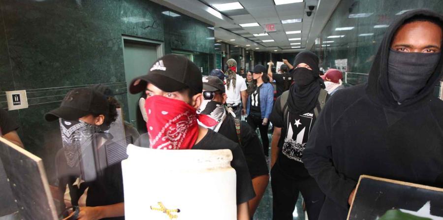 Manifestantes cargan pancartas y cantan consignas en el vestíbulo del edificio. (horizontal-x3)