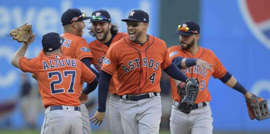 Los jugadores de los Astros de Houston George Springer (4) y el venezolano José Altuve se felicitan, mientras sus compañeros empiezan la celebración luego de vencer a los Indios de Cleveland. (AP / David Dermer) (horizontal-x3)