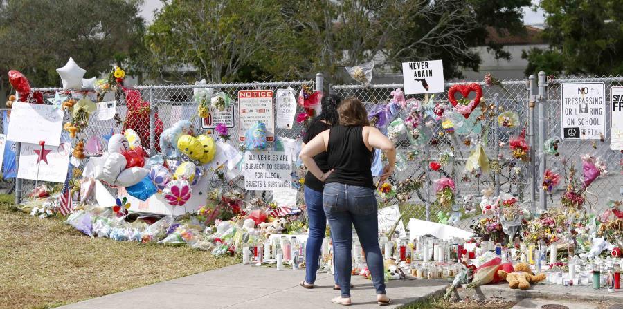 Dos personas observan un altar improvisado en memoria de las víctimas del tiroteo en la Escuela Secundaria Marjory Stoneman Douglas en Parkland, Florida. (horizontal-x3)
