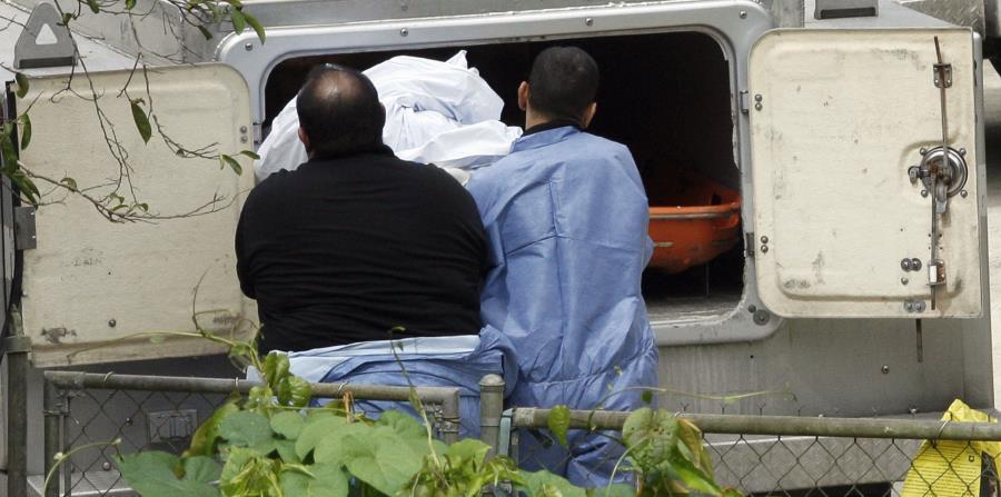 Personal del Instituto de Ciencias Forenses coloca en un vehículo especializado un cadáver. (GFR Media) (horizontal-x3)
