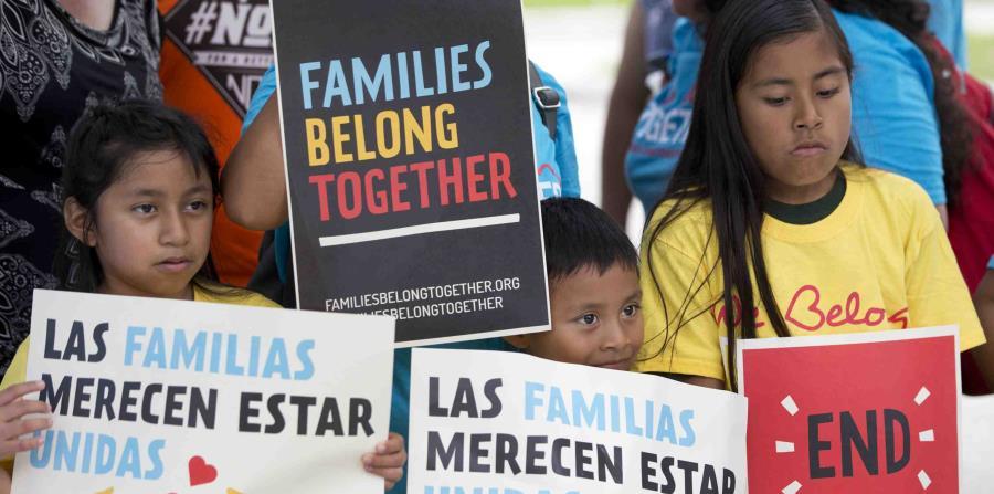 niños sosteniendo carteles durante una manifestación enfrente de la oficina del Servicio de Control de Inmigración y Aduanas en Miramar, Florida. (AP (horizontal-x3)