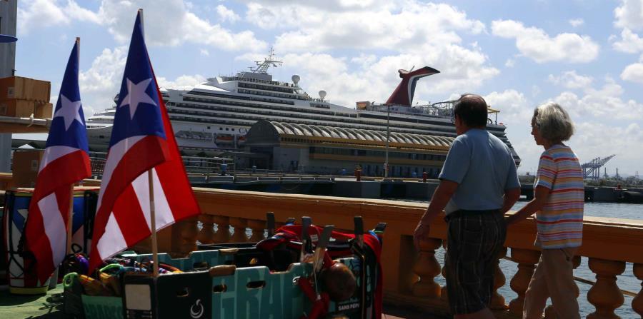 dos turistas paseando frente a un crucero en el Puerto de San Juan (horizontal-x3)