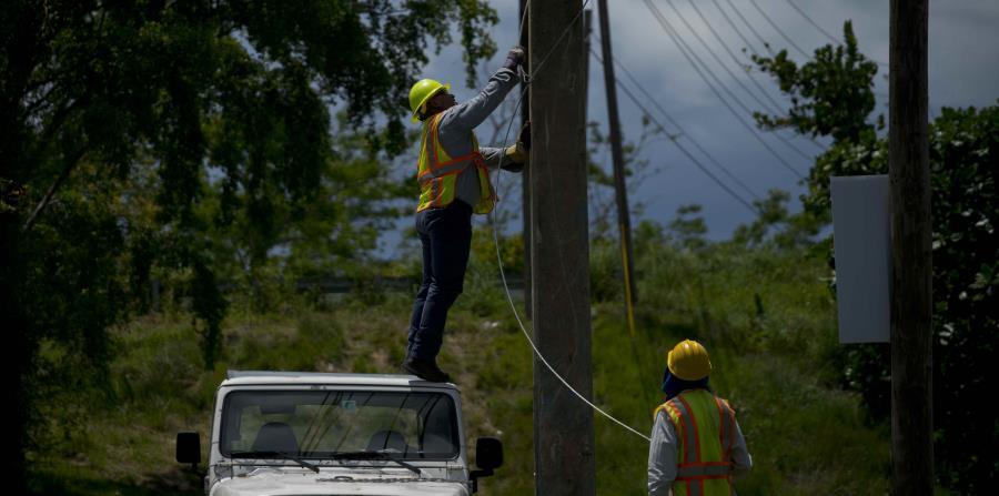 Trabajadores de la brigada de reparaciones eléctricas retiran viejos cables de un poste en San Germán. (AP) (horizontal-x3)
