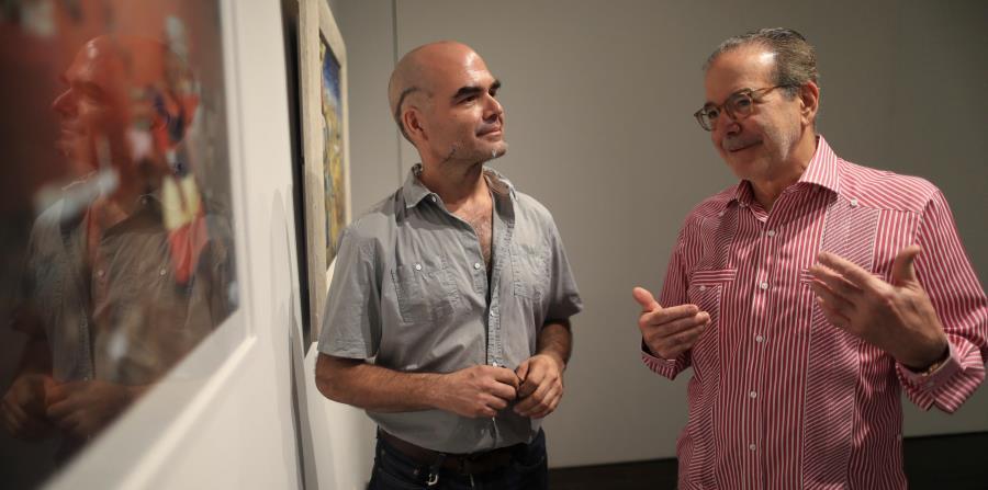 Ignacio Cortés y Juhasz en la galería de una de las exhibiciones, que  incluyen diferentes materiales- fotografías, pinturas, documentos, videos, instalaciones y otros elementos. (horizontal-x3)
