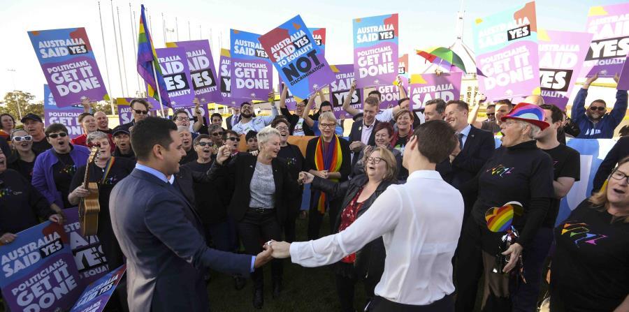 Activistas y voluntarios paritdarios del matrimonio homosexual corean lemas mientras piden a los legisladores que modifiquen la ley para legalizar el matrimonio homosexual, en una marcha ante el Parlamento en Canberra, Australia (horizontal-x3)