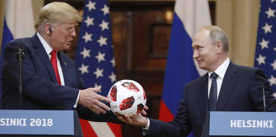 Trump recibe un balón de fútbol de manos del presidente ruso Vladimir Putin. (AP) (horizontal-x3)