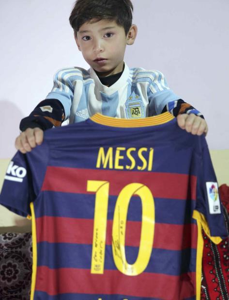 Murtaza Ahmadi, aficionado de Lionel Messi, muestra el autógrafo del astro argentino en una camiseta en la casa de unos familiares en Kabul, Afganistán el viernes 7 de diciembre de 2018. (AP) (vertical-x1)