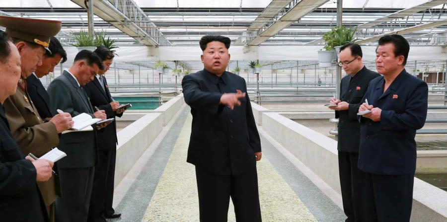 El líder norcoreano Kim Jong-un (al centro) durante una visita a una fábrica en un lugar sin identificar en Corea del Norte. (EFE) (horizontal-x3)