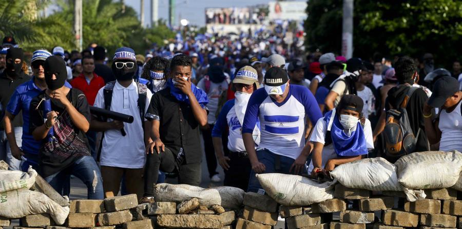 Manifestantes antigubernamentales se ponen a cubierto detrás de una barricada tras enfrentamientos durante una marcha contra el gobierno de Daniel Ortega, en Managua, Nicaragua. (AP) (horizontal-x3)