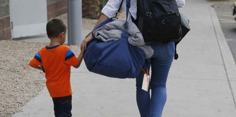 José Jr., de 3 años y natural de Honduras, recibe ayuda de una trabajadora del Southern Poverty Law Center antes de reunirse con su padre, el 10 de julio de 2018, en Phoenix. (AP (horizontal-x3)