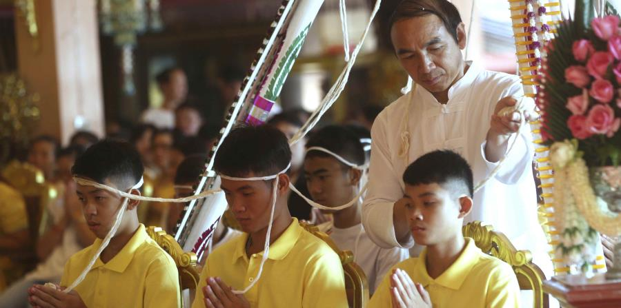 El entrenador Ekkapol Janthawong (centro) y niños del equipo de fútbol rescatado de una cueva anegada durante una ceremonia budista que se cree que prolonga la vida de los asistentes además de alejarlos de peligros y desventuras, en el distrito de Mae Sai (horizontal-x3)