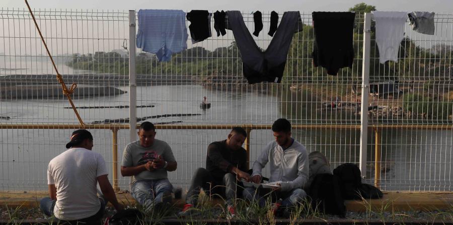 Un grupo de inmigrantes esperan por el permiso para entrar a México. (AP) (horizontal-x3)