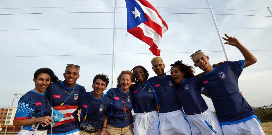 Parte de la delegación de Puerto Rico posa junto a la bandera a pocos días de los Juegos Centroamericanos y del Caribe. (horizontal-x3)