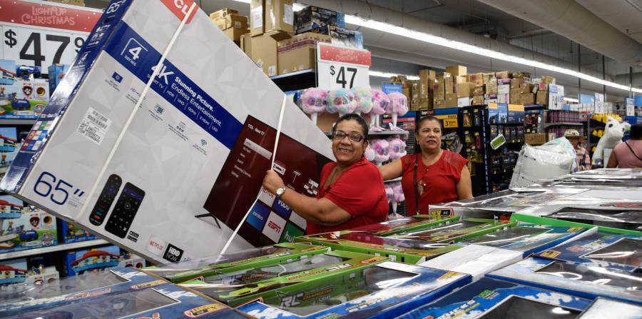Una clienta carga con un televisor de 65 pulgadas hacia la caja registradora. (Gabriella Báez / Especial GFR Media) (horizontal-x3)