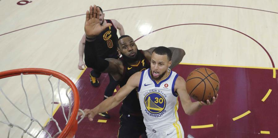 LeBron James, de los Cavaliers de Cleveland, intenta evitar que Stephen Curry, de los Warriors de Golden State, enceste. (AP) (horizontal-x3)