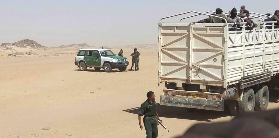 gendarmes argelinos, armados con fusiles AK-47, suben a migrantes a camiones para dejarlos en la frontera con Níger. Muchos migrantes mueren después en su marcha por el desierto hacia Níger. (horizontal-x3)