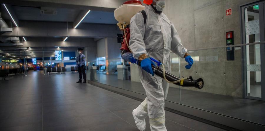 Un trabajador del Aeropuerto Internacional Liszt Ferenc de Budapest, en Hungría, desinfecta uno de sus pasillos como medida de precaución contra la propagación del coronavirus. (AP Photo)