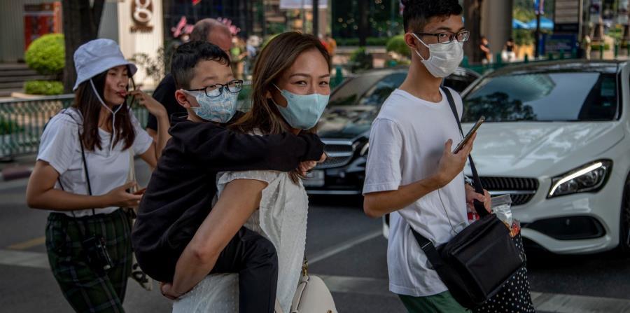 Una familia china camina por Bangkok, Tailandia, con máscaras faciales. (AP Photos)
