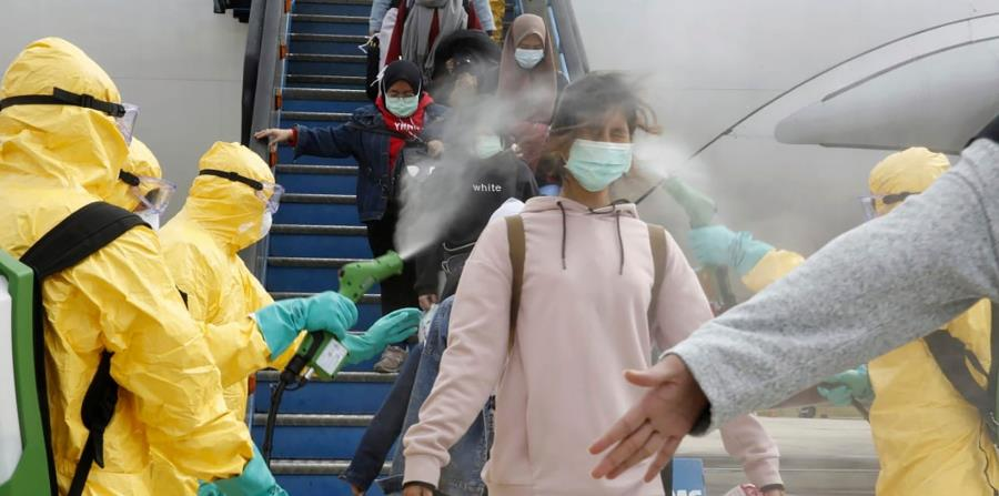 Los indonesios que llegaron en un avión de Wuhan, China, fueron rociados con antiséptico en el aeropuerto Hang Nadim en Batam, Indonesia. (AP Photo)