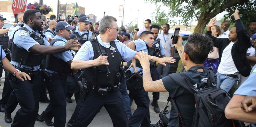 Agentes del Departamento de Policía de Chicago confrontan a una multitud enargdecida tras la muerte a tiros de un hombre a manos de agentes en Chicago, el sábado 14 de julio de 2018. (AP) (horizontal-x3)