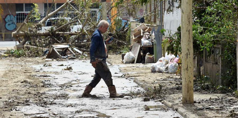 Un hombre cruza una calle llena de fango y escombros en el barrio Buenos Aires en Arecibo. (horizontal-x3)