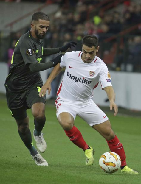 Wissam Ben Yedder (der.), del Sevilla, lucha por mantener control del balón contra Medhi Carcela. (AP / Olivier Matthys) (vertical-x1)