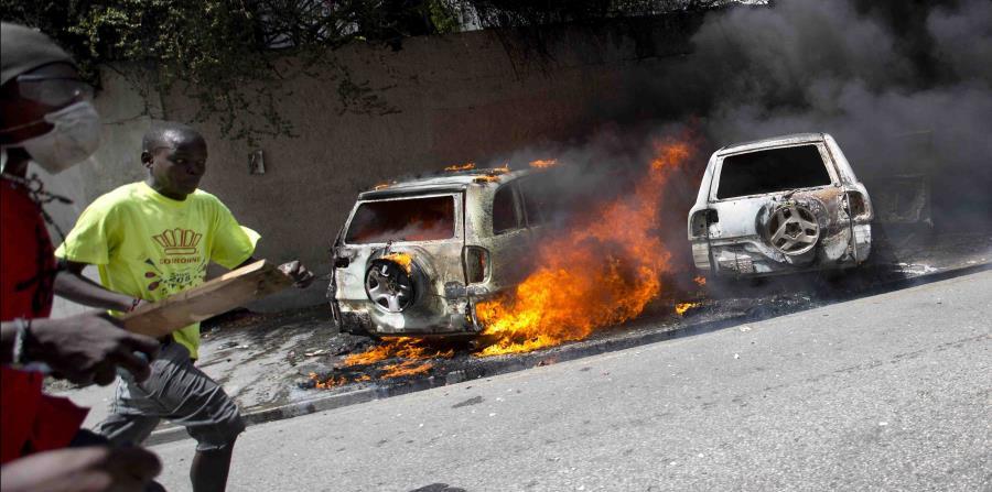 Personas corren luego que protestantes prendieron fuego a varios automóbiles durante los disturbios en Haití por el alza en el precio de los combustibles. (AP / Dieu Nalio Chery) (horizontal-x3)