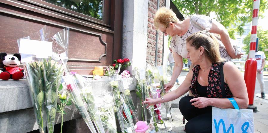 Varias personas colocan flores como homenaje a las víctimas del tiroteo de ante el Café 'Les Augustins', de Lieja, Bélgica (horizontal-x3)