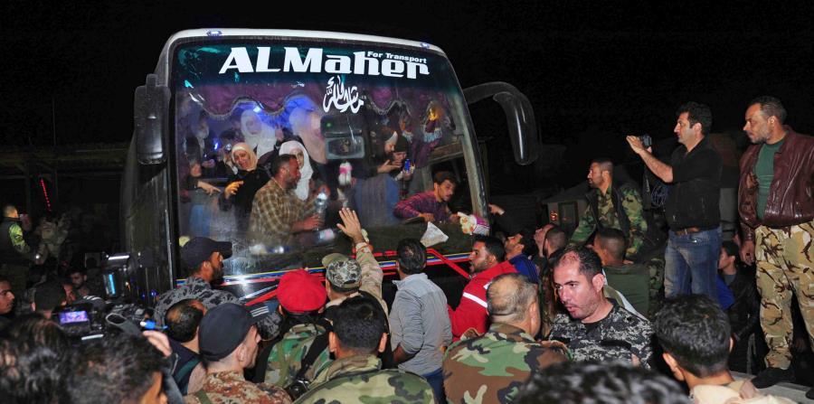 En esta imagen, distribuida por la agencia oficial de noticias siria SANA, soldados y residentes saludan a civiles tras ser liberados por el grupo Ejército del Islam, que los tenía retenidos desde 2013, en Damasco, Siria, (horizontal-x3)